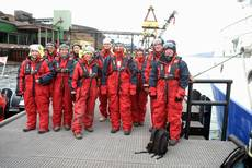 Skupina v overalech, připravena na dlouhou plavbu po Isfjordu do Longyearbyenu na otevřených člunech