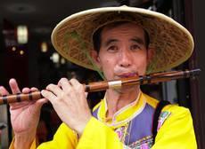 Číňan hrající na flétnu